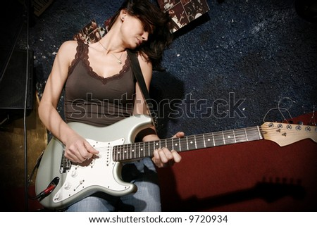 Woman playing guitar at the club - stock photo