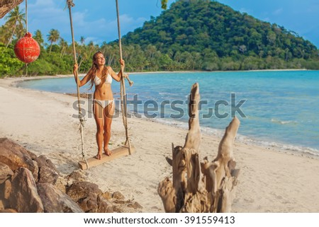 woman playing on a swing on a beach  - stock photo