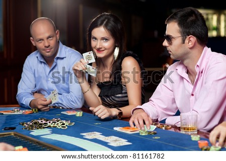 woman playing poker with men, holding an ace and a king - stock photo