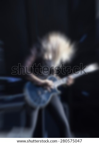 woman playing rock guitar on concert,blurred rock background - stock photo