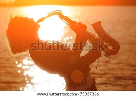Woman playing saxophone sax at sunset beach. - stock photo