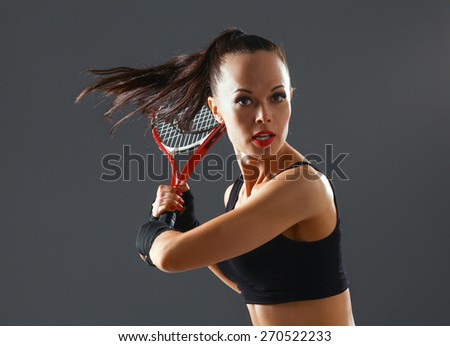 Woman playing tennis on gray background . - stock photo
