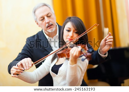 Woman playing the violin with a teacher - stock photo