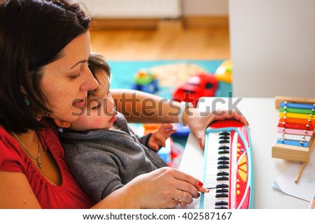 Woman playing with child on a toy piano on table - stock photo