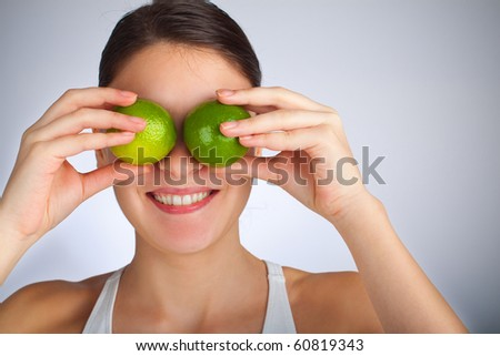 Woman playing with limes - stock photo