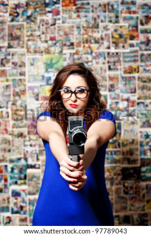 Woman pointing a vintage camera on a comic theme background - stock photo