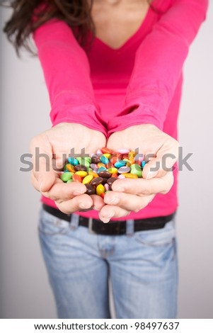 woman portrait holding lot of candy in her hands - stock photo