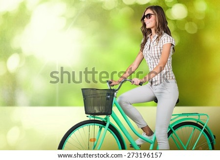 Woman. Portrait of young woman riding bicycle against brick wall - stock photo