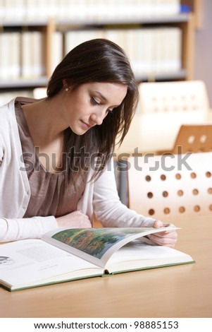 woman portrait: student reading a book at library - stock photo