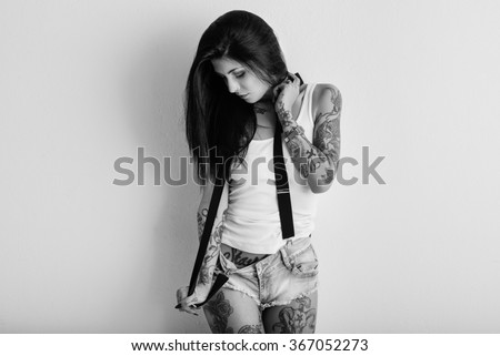 Woman portrait with tattoo and suspenders against white wall. Black and white image. - stock photo