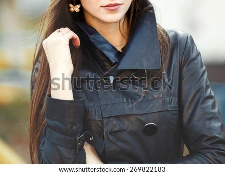 Woman posing against break wall, wearing leather jacket.  - stock photo