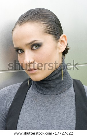 Woman posing against gray cement wall on a bright day - stock photo