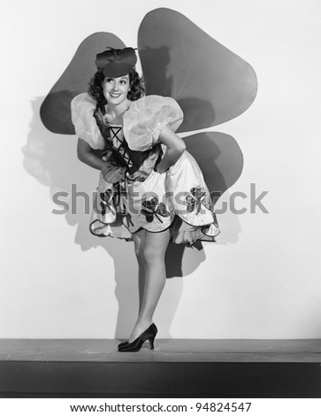 Woman posing in front of large shamrock - stock photo