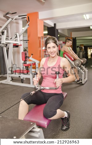Woman posing in gym at rowing fitness machines and guy in the background - stock photo