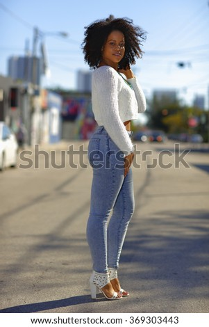 Woman posing in the middle of the road in denim jeans - stock photo