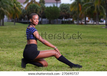 Woman posing on a field of grass in the park - stock photo