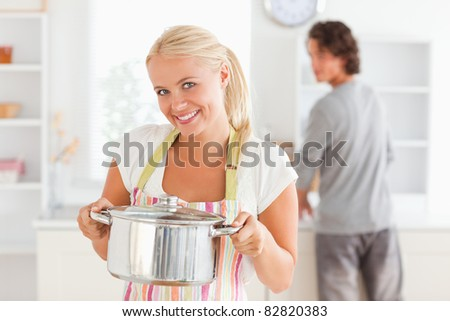 Woman posing with a boiler while her fiance is washing the dishes in their kitchen - stock photo