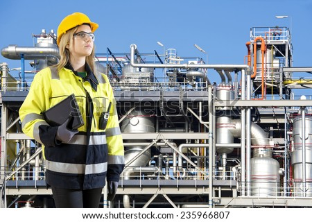 Woman, posing with a tablet and cb radio in front of a petrochemical installation as plant and safety officer - stock photo