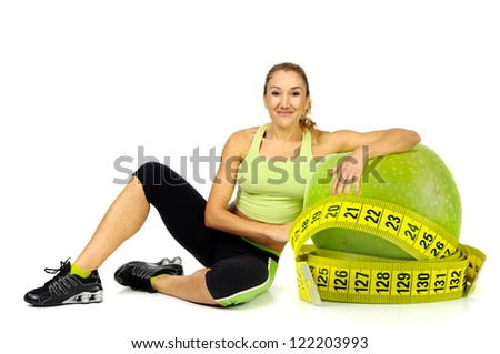 woman posing with apple and measuring tape isolated in white - stock photo