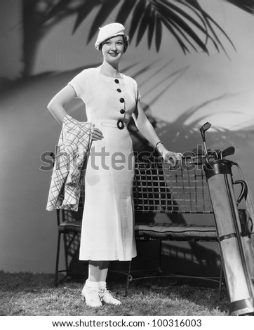 Woman posing with golf clubs - stock photo