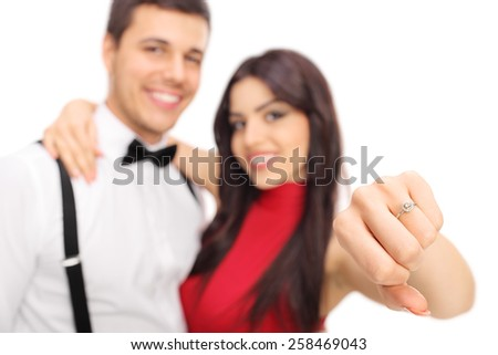 Woman posing with her fianc���©e and showing her engagement ring with the focus on the ring isolated on white background - stock photo