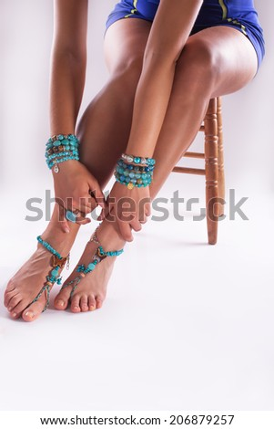 Woman posing with summer styles bracelets and rings, studio shot - stock photo