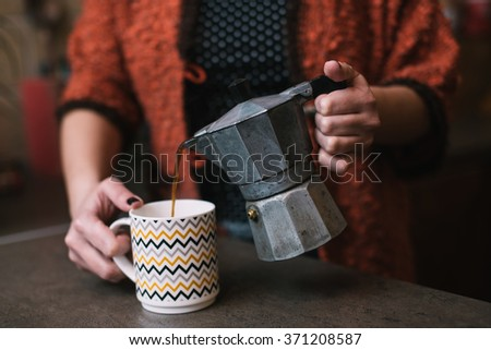 Woman pouring coffee from vintage coffee maker - stock photo