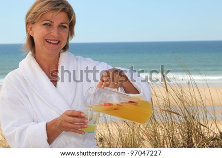 Woman pouring herself a glass of orange juice at the beach - stock photo