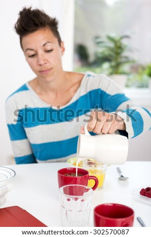 Woman pouring milk in her morning coffee at the breakfast table. - stock photo