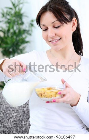 Woman pouring milk onto a bowl of cereal - stock photo