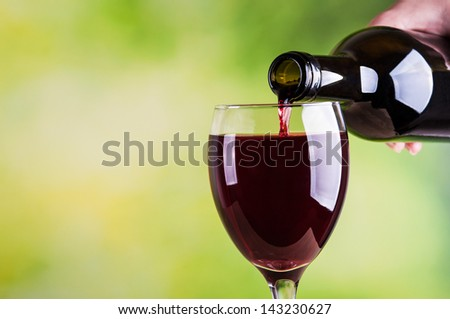 Woman pouring red wine into glass - stock photo