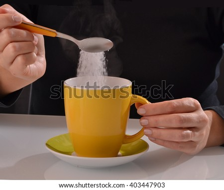 Woman pouring sugar on coffee cup. - stock photo
