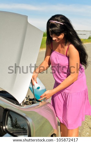 Woman pours a liquid for washing glasses to the car - stock photo