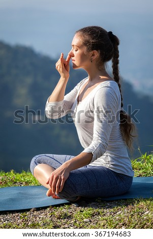 Woman practices pranayama yoga breath control in lotus pose padmasana outdoors in Himalayas in the morning on sunrise. Himachal Pradesh, India - stock photo