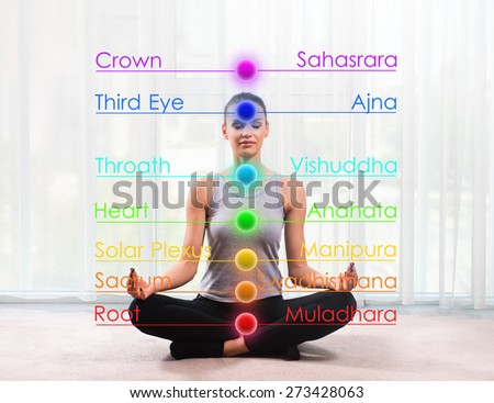 Woman practicing meditation with chakras marked - stock photo