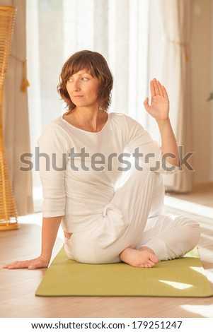 Woman practicing yoga and posing in her yoga studio. - stock photo