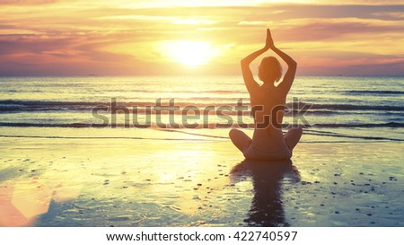 Woman practicing yoga at seashore during sunset. - stock photo