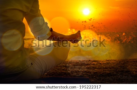 Woman Practicing Yoga by the Sea at Sunset. Beautiful Toned Photo with Golden Bokeh. Healthy Lifestyle Concept. - stock photo