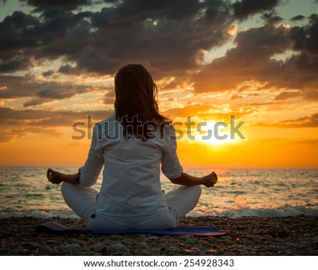 Woman Practicing Yoga by the Sea at Sunset. Rear View. Dramatic Sky. Healthy Lifestyle Concept. - stock photo