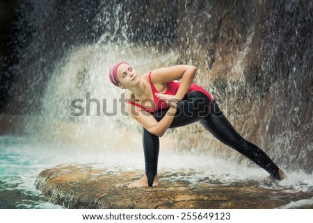 Woman practicing yoga near waterfall. Revolved Side Angle. Parivrtta Parsvakonasana - stock photo