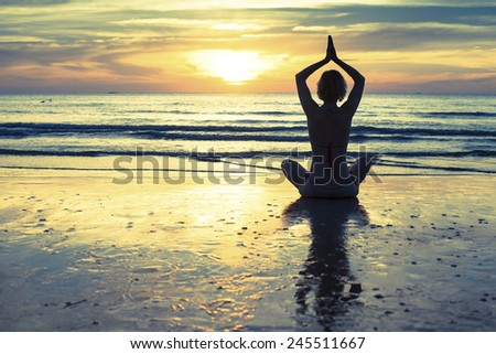 Woman practicing yoga on the beach at sunset in Thailand. - stock photo
