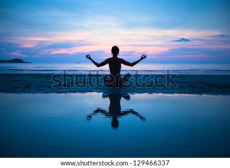 Woman practicing yoga on the beach at sunset (with reflection in water) - stock photo