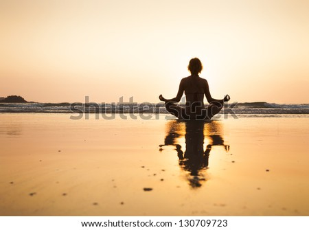 Woman practicing yoga on the beach, lotus position at Koh Chang, Thailand - stock photo