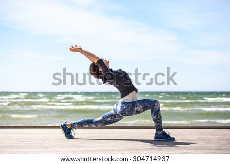 woman practicing yoga on the coast of sea, sunny day - stock photo