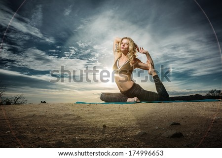 Woman practicing yoga outdoors over sunset sky background.  - stock photo