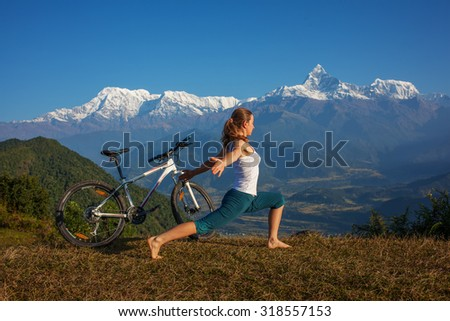 woman practicing yoga, relaxing after riding bikes high in mountain - stock photo