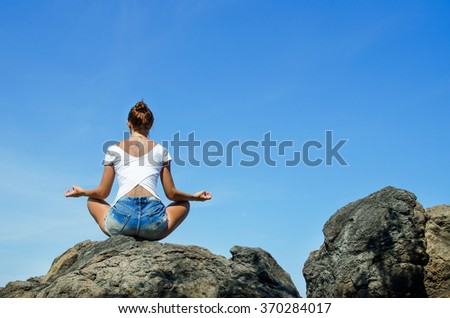 Woman practicing yoga sitting on a rock in front of the azure ocean. Stock image - stock photo