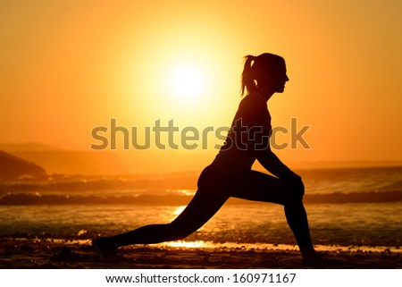 Woman practicing yoga, stretching and relaxing exercises on the beach at sunset. Female athlete silhouette exercising on towards the sea on bright golden sun background. - stock photo