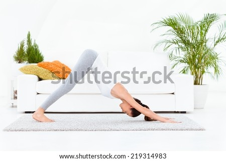 Woman practising yoga at home - Downward Facing Dog - Adho Mukha Svanasana - stock photo