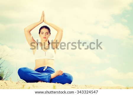 Woman practising yoga on a beach. - stock photo